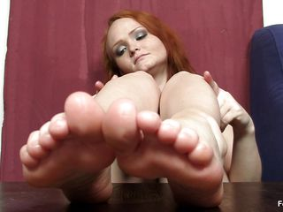 This woman really wants to wrap her feet around a cock and make it cum, but unfortunately she does not have a cock handily available. Therefore, she is making use of the next best thing, which is a nasty big black dildo standing up right on the table. She is caressing that with her feet.