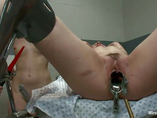 Three sluts are giving this cutie a treatment she will never forget. They've putted her on the gynecologist table and performed some pussy pleasuring first by gaping that cunt with a metal speculum and then rubbing it with a vibrator. It seems that the bitch enjoys it and get's kissed on her pink lips by the brunette